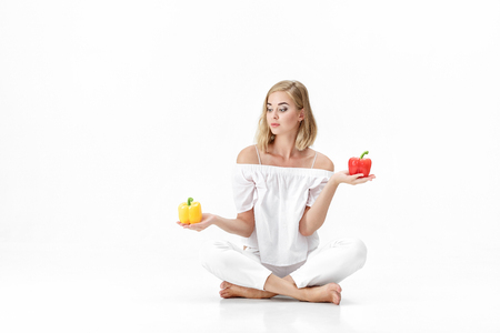 hand bell: beautiful blond woman in white blouse chooses yellow or red bell pepper. Health and Diet Stock Photo