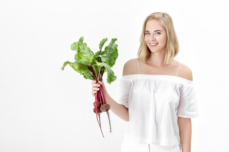 Beautiful blond woman holds beetroot with green leaves on white background. Health and vitamins