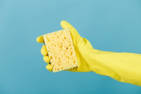 hand  in yellow glove holding sponge on blue background. cleaning Stock Photo