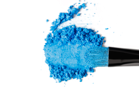Broken blue eye shadow and brush isolated on white background