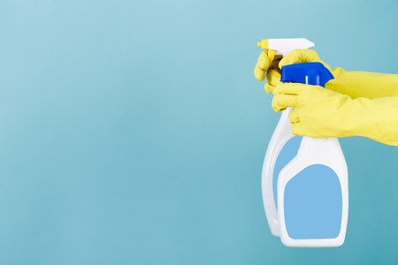 La mano in guanto giallo tiene la bottiglia dello spruzzo di detersivo liquido su fondo blu. pulizia