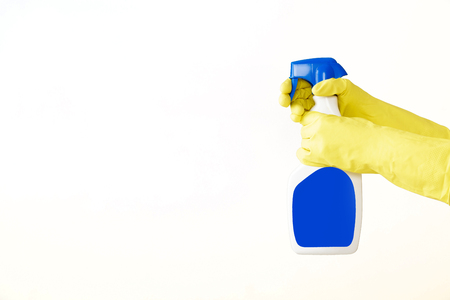 Hand in rubber yellow glove holds  spray bottle of liquid detergent on white background. cleaning Stock Photo