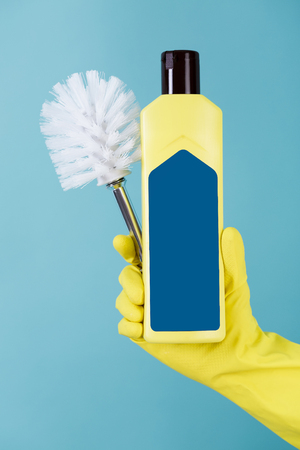 colored bottle: Hand in yellow glove holds bottle of liquid detergent for toilet and brush on blue background.