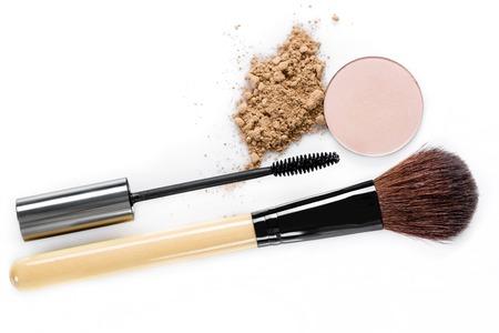 crushing: Mascara, beige powder for face, eye shadow and makeup brush  on white background