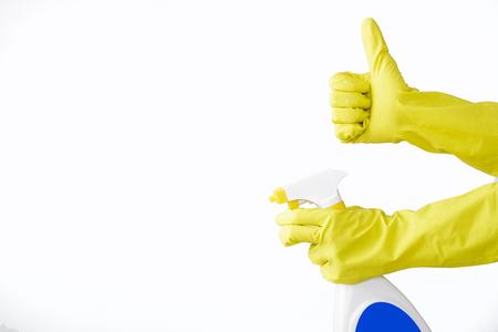 Mano in guanto di gomma gialla tiene bottiglia spray di detergente liquido su sfondo bianco. pulizia Archivio Fotografico