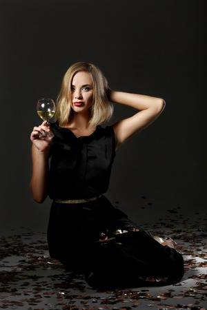 黒の背景に白ワインをグラスで美しい金髪の女性