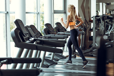 athletic blond woman running on treadmill at gym. Imagens