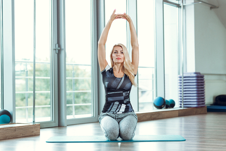 Young slender blond woman doing exercises in gym