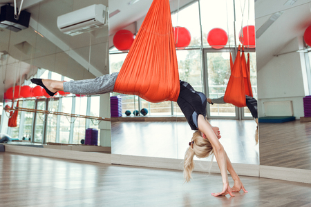 Fly yoga. Young woman practices anti-gravity yoga with hammock .