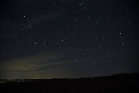 Beautiful night sky with stars.  clouds  over field