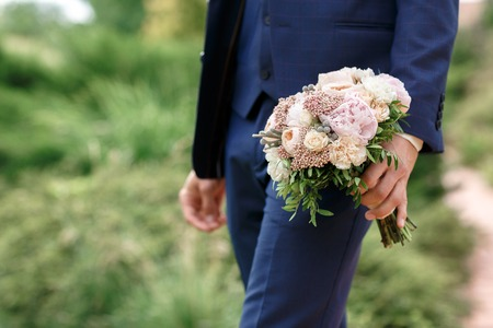 The groom holding a beautiful wedding bouquet of peonies