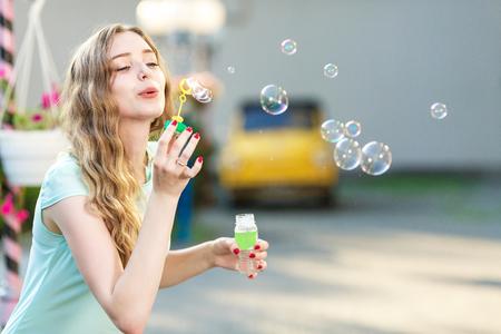 happy woman blowing soap bubbles Imagens