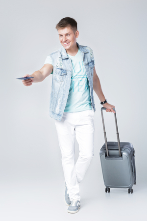 young man in blue shirt with suitcase