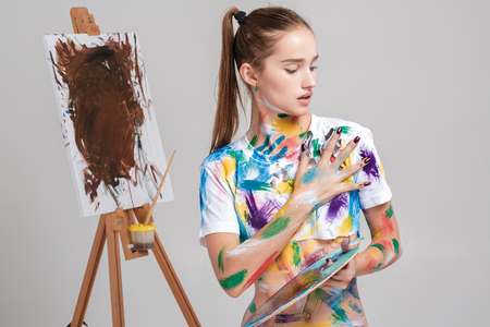 woman painter soiled in colorful paint draws on canvas.