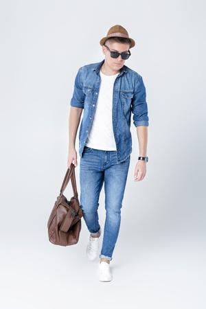 man in denim holding leather bag Banco de Imagens