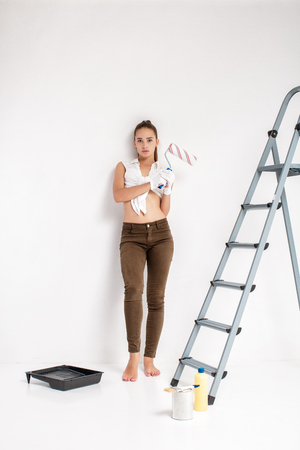 woman painting a wall in house Imagens