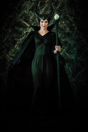 レインコートと角の妖精魔法使いとして服を着た女性