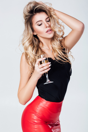 woman holding glass of champagne and bottle