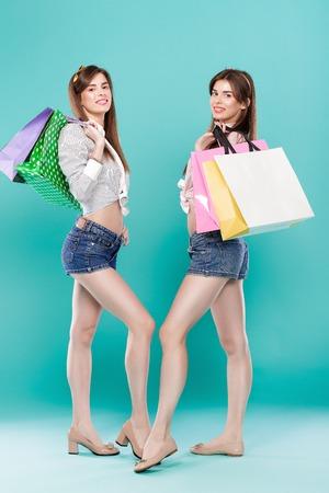 gemelli femminili con borse della spesa su sfondo blu.