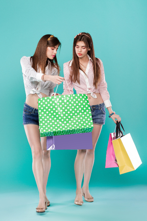 female twins with shopping bags on blue background.