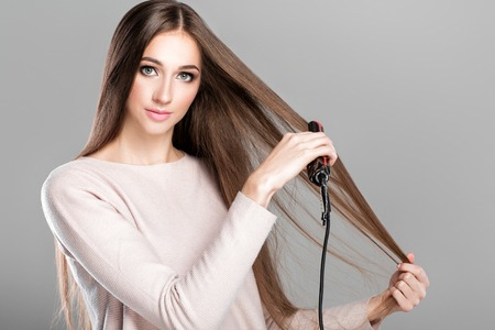 woman ironing hair with hair iron. Stock Photo