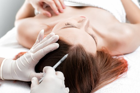 Needle mesotherapy. Cosmetic been injected in womans head.