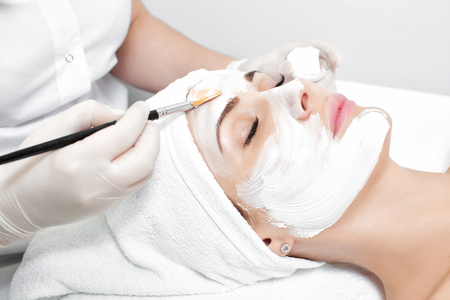 beautician applies mask to the face of  woman