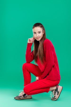 woman in red sweater on green background