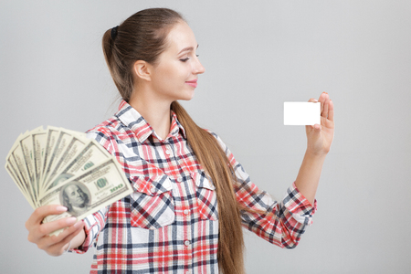woman holds dollar bills and plastic card.