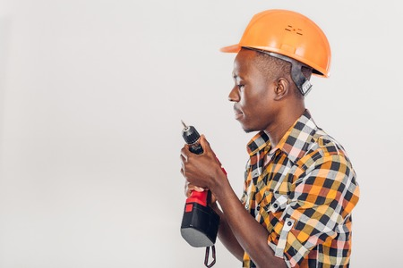 African American worker uses electric screwdriver