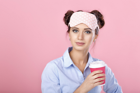 woman in mask for sleeping drinks morning coffee