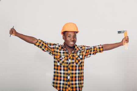 African-American builder uses measuring tape