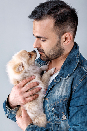 man in denim jacket holds pomeranian dog. Stock Photo