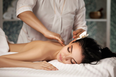Relaxed woman receiving massage Stock Photo