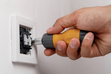 electrician installing light switch Banco de Imagens