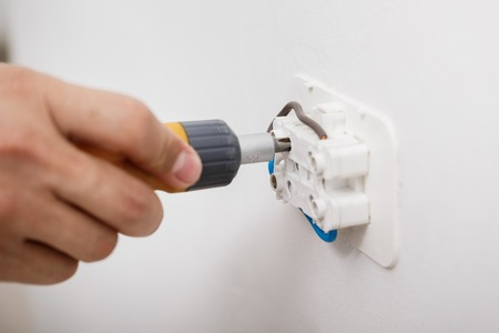 electrician installing electrical socket Stock Photo