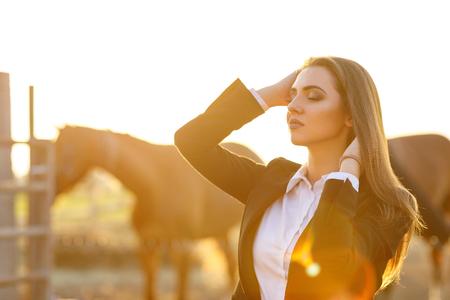 donna cavaliere con frusta al tramonto Archivio Fotografico