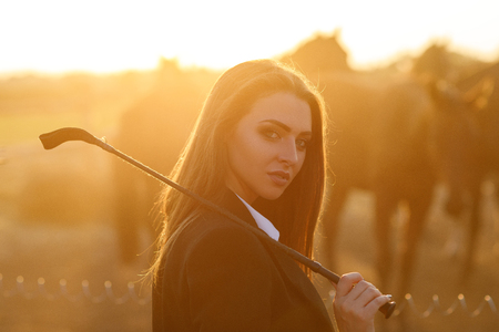 rider woman with whip at the sunset Archivio Fotografico