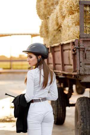 rider woman in helmet stands near stables