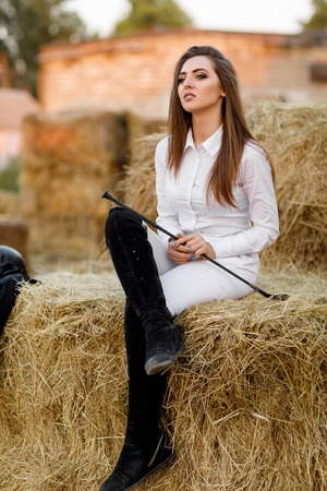 rider woman with whip is sitting on hay Imagens
