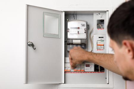 Electrical terminal box. man turn on or off Standard-Bild
