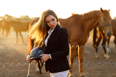 rider woman with whip at the sunset Stock Photo