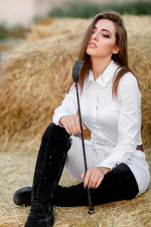 rider woman with whip is sitting on hay 写真素材