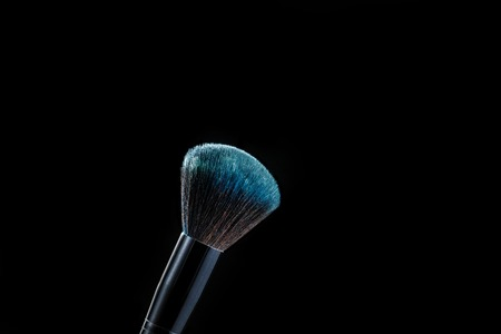 makeup brush with powder on black background Imagens