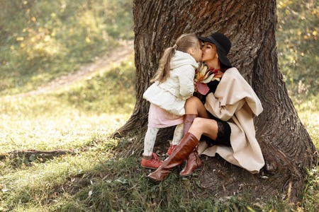 mother kissing her little daughter girl near the tree