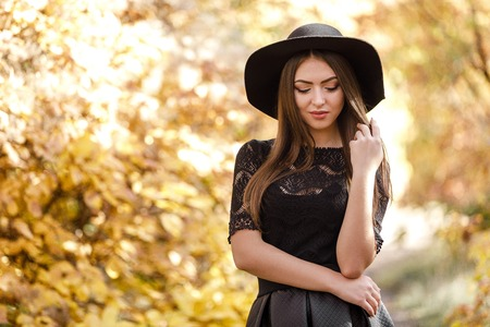 beautiful woman in black dress and hat in autumn