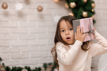 Pretty smiling girl holding Christmas gift in hand