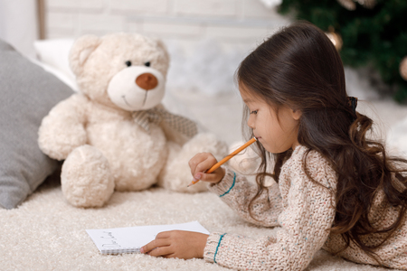 Cute child girl writing letter to Santa Claus at home