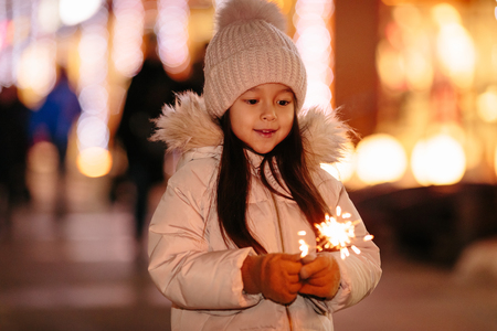 Cute smiling little girl with bengal lights on the street in the evening Standard-Bild