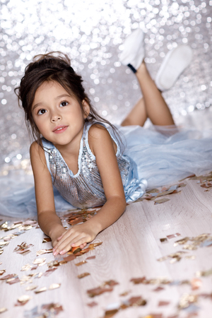 little girl in blue dress sitting on the floor with confetti